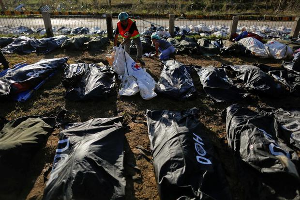 Forensic experts work on a mass grave with more than 700 bodies of victims of Typhoon Haiyan just outside Tacloban today