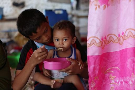 A young baby eats in a temporary shelter in Tacloban on the Island of Leyte, Philippines. Photo:Julien Behal/Maxwells