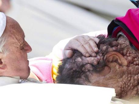 Pope Francis caresses a sick person in Saint Peter's Square at the end of his General Audience in Vatican City