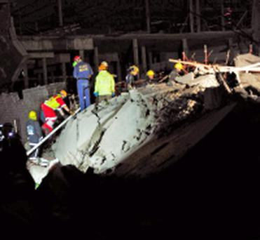 Paramedics look for people trapped in a mall that collapsed in Tongaat, South Africa