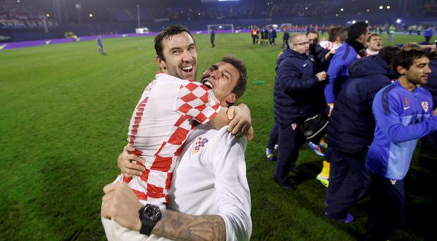 Croatia's Darijo Srna (L) and Mario Mandzukic celebrate defeating Iceland after their 2014 World Cup playoff soccer match in Zagreb