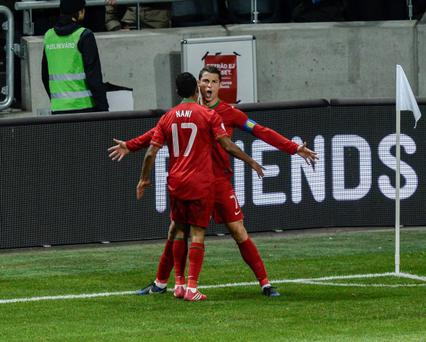 Portugal's Cristiano Ronaldo celebrates scoring the opening goal with teammate Nani, during the World Cup 2014 qualifying playoff second leg soccer match between Sweden and Portugal at Friends Arena in Stockholm