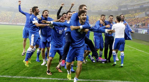 The Greece team celebrate after defeating Romania in their World Cup qualifying playoff second leg match at the National Arena in Bucharest