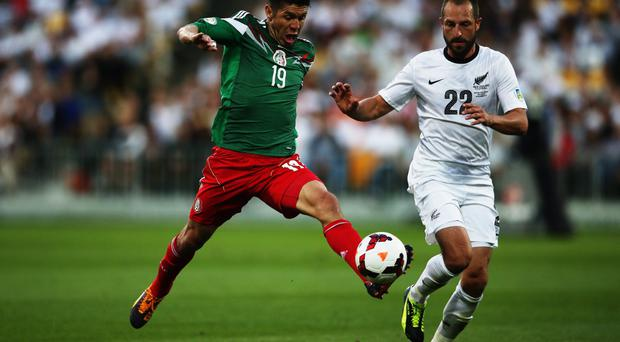Oribe Peralta of Mexico reaches out for the ball past Andrew Durante of New Zealand during leg 2 of the FIFA World Cup Qualifier match between the New Zealand All Whites and Mexico at Westpac Stadium this morning