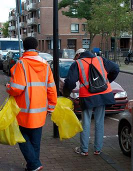 Chronic alcoholics clean a street in Amsterdam. The initiative of street cleaning in exchange for beer is sponsored by the De Regenboog