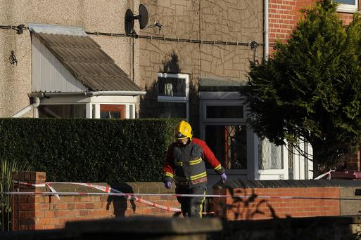 A member of the Fire and Rescue Service leaves the scene of a house fire on Williamthorpe Road in North Wingfield, Chesterfield, where four people, including two children, have been killed