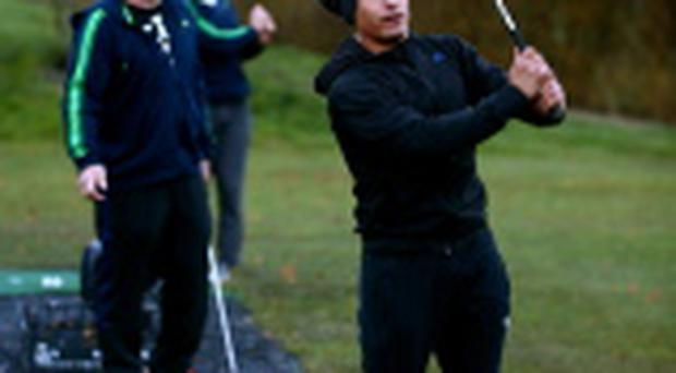 Aaron Smith of the New Zealand All Blacks hits golf balls on the driving range with Andrew Hore and Tom Taylor at the Castleknock Golf Club