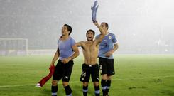 Luis Suarez (L), Nicolas Lodiero and Diego Godin of Uruguay celebrate at the end of their 2014 World Cup qualifying playoff second leg soccer match against Jordan in Montevideo