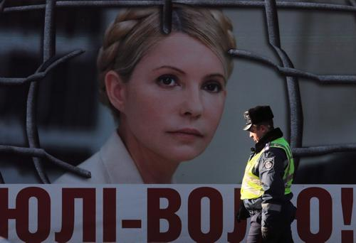 An Interior Ministry officer walks past a board displaying a portrait of jailed former Ukrainian Prime Minister and opposition leader Yulia Tymoshenko at a protest tent camp set up by Tymoshenko's supporters in central Kiev