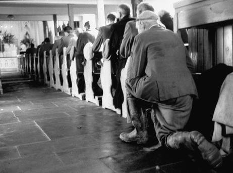 A man kneels in respect at a funeral Mass for the late John F Kennedy