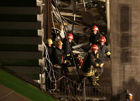 Firefighters move a body out from the collapsed Maxima supermarket in Riga