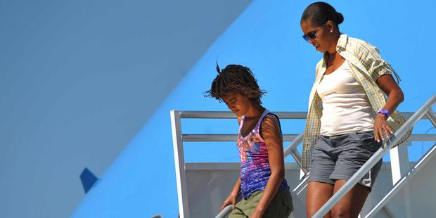 First Lady Michelle Obama and daughter Malia step off Air Force One August 16, 2009 upon arrival at Grand Canyon National Park Airport in Grand Canyon, Arizona. Obama and his family will spend the day visiting the Grand Canyon. AFP PHOTO/Mandel NGAN (Photo credit should read MANDEL NGAN/AFP/Getty Images)