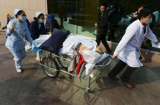 An injured woman is transferred to a hospital after an explosion at a Sinopec Corp oil pipeline in Huangdao, Qingdao, Shandong Province