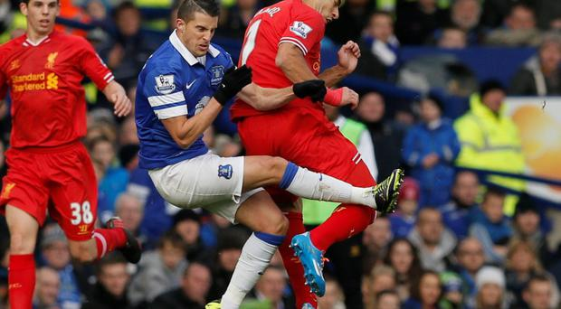 Liverpool's Luis Suarez (R) is fouled by Everton's Kevin Mirallas during their English Premier League soccer match at Goodison Park