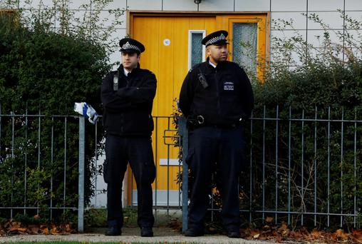 Police stand guard in front of a property in Lambeth, south London November 23, 2013.