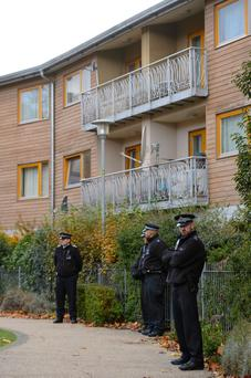 Police officers stand outside flats in Brixton, south London, as police are conducting house-to-house inquires in the area where three women were allegedly held as slaves for at least 30 years were rescued