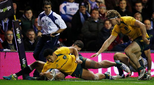 Australia's Chris Feauai-Sautia (C) scores a try against Scotland