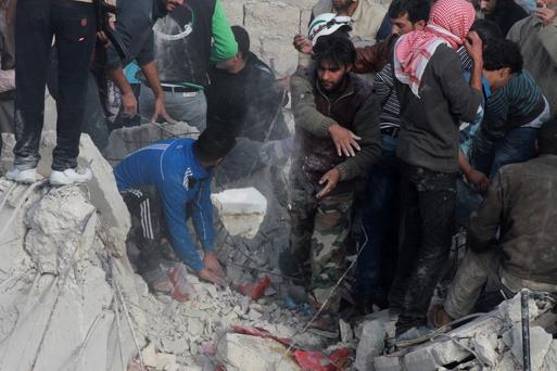 People search for survivors amid the rubble of collapsed buildings after what activists said was shelling by forces loyal to Syria's President Bashar al-Assad in the Karam el-Beik district of Aleppo November 23, 2013.
