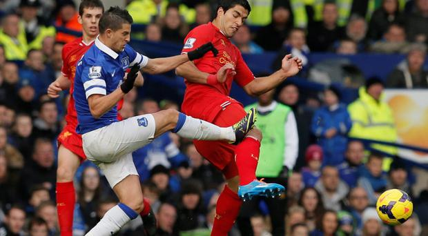Liverpool's Luis Suarez (R) is fouled by Everton's Kevin Mirallas