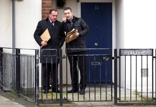 Plainclothes police officers make door-to-door inquiries in Brixton, south London, November 24, 2013. Three women enslaved in a house in London for 30 years lived there in some kind of