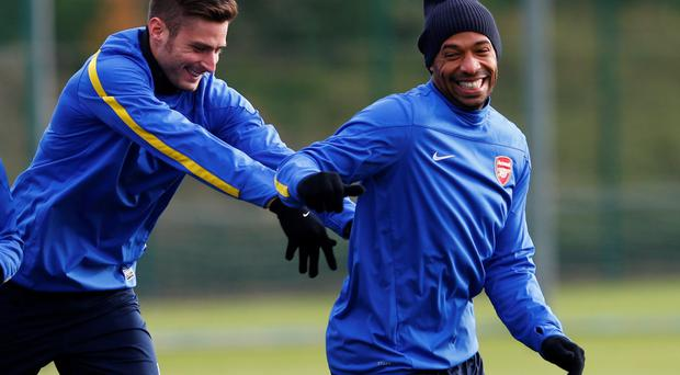Arsenal's Olivier Giroud (L) pushes Thierry Henry during a team training session at Arsenal's training ground in London