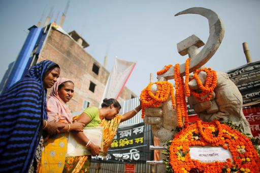 Relatives of garment workers, who died in the Rana Plaza building collapse, cry as they pay tribute in front of a sculpture after a protest in front of the site in Savar November 24, 2013
