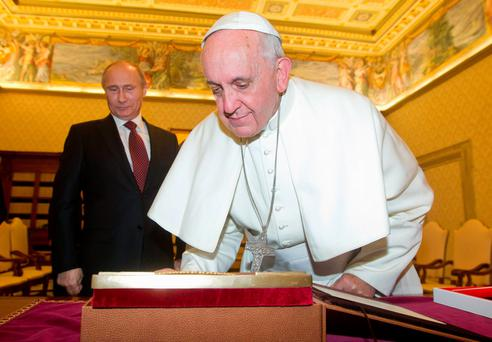 Pope Francis (R) exchanges gifts with Russia's President Vladimir Putin during a private audience at the Vatican, November 25, 2013