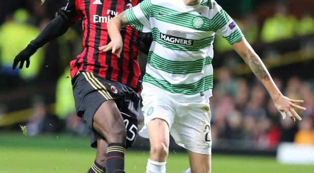 Celtic's Mikael Lustig challenges AC Milan's Mario Balotelli during the UEFA Champions League match at Celtic Park, Glasgow