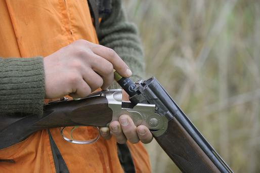 Stock image: Hunter loading shotgun