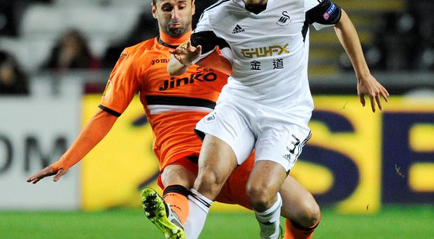 Swansea City's Neil Taylor (R) is challenged by Valencia's Jonas tonight