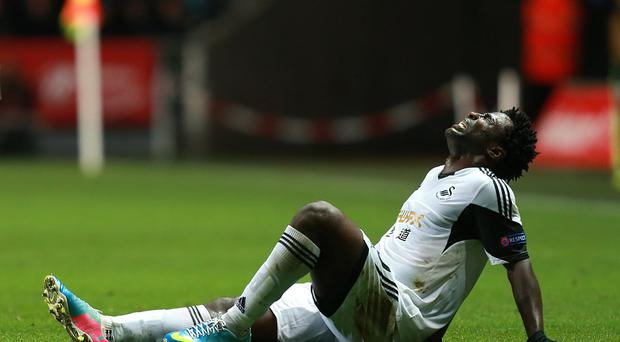Swansea City's Wilfried Bony sits injured on the pitch