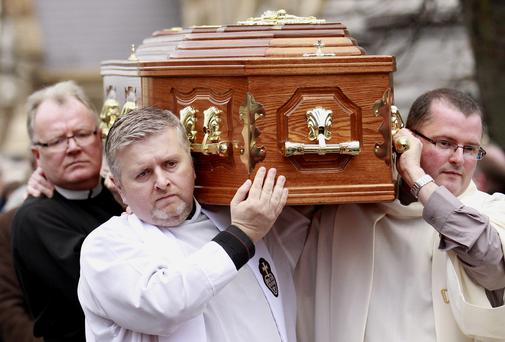 Priests carry the coffin of Catholic Priest Alec Reid from Clonard Monastery, West Belfast