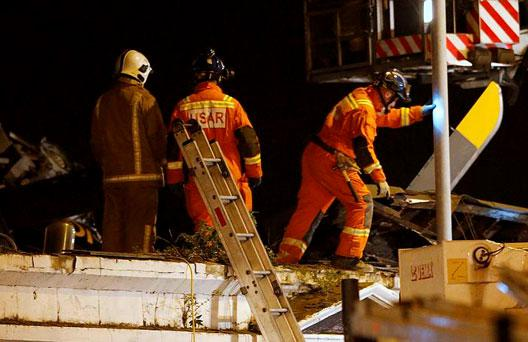 Rescue workers examine the wreckage of a police helicopter which crashed onto the roof of the Clutha Vaults pub in Glasgow