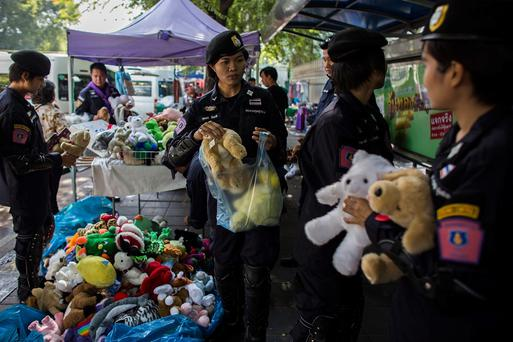 BANGKOK, THAILAND - NOVEMBER 30: Police officers buy toy dolls from a vendor as they guard inside the government house area on November 30, 2013 in Bangkok, Thailand. Anti-government protesters in Bangkok say they plan to occupy the government house and the zoo, demonstrators calling on the government to step down have marched on ministries and government bodies in an attempt to shut them down. (Photo by Lam Yik Fei/Getty Images)