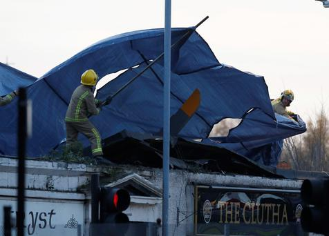 Rescue workers cover the wreckage of a police helicopter which crashed onto the roof of the Clutha Vaults pub in Glasgow, Scotland November 30, 2013. The police helicopter crashed into the pub in Glasgow on Friday night, causing multiple injuries as dust and debris was thrown across the busy drinking hole during a concert, eye witnesses said. Scotland's first minister, Alex Salmond, said people should prepare for the likelihood of fatalities. Three people were on board the helicopter, police said. REUTERS/Russell Cheyne