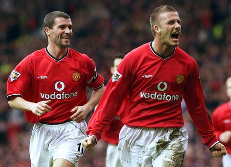 Manchester United's David Beckham (R) celebrates scoring against Sunderland with captain Roy Keane (L) during their English premier league match at Old Trafford, Manchester, February 2, 2002. REUTERS/Ian Hodgson