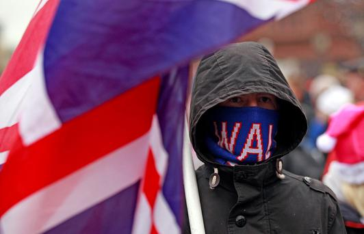 A Loyalist covers his face with a scarf as he takes part in a march from the City Hall