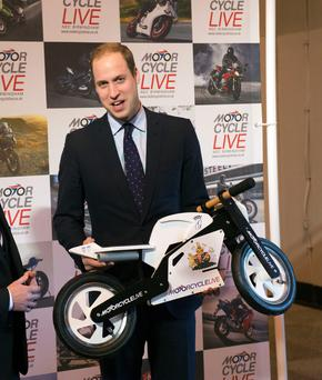The Duke of Cambridge receives a gift for his son Prince George from exhibition director Dean Linehan (not pictured) during his visit to Motorcycle Live at the NEC