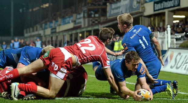 Eoin Reddan, Leinster, goes over to score a try despite the tackle of Josh Lewis