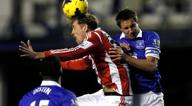 Everton's Phil Jagielka (R) challenges Stoke City's Peter Crouch (C) during their English Premier League soccer match at Goodison Park in Liverpool