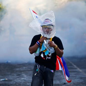 An anti-government protester wears a plastic bag over his head as protection from teargas during clashes with police