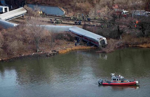Emergency workers gather at the site of a Metro-North train derailment in the Bronx borough of New York