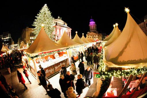 People visit the illuminated Christmas market at Gendarmenmarkt square in Berlin