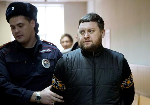Yuri Zarutsky, right, a suspect of carrying out an acid attack on Bolshoi ballet's director that exposed vicious backstage bickering and intrigue at the renowned theater, is escorted to a court room in Moscow