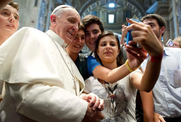Some teens use their phone to take a selfie with Pope Francis. Photo from 2013