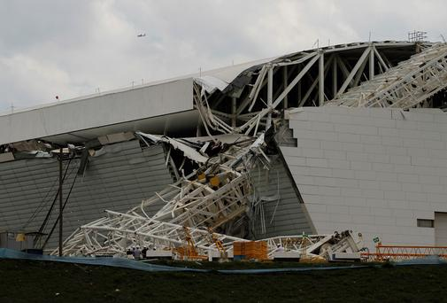Workers stand near a crane that collapsed on the site of the Arena Sao Paulo stadium