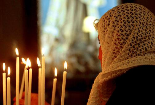 A woman lights candle in the Church of the Nativity in Bethlehem.