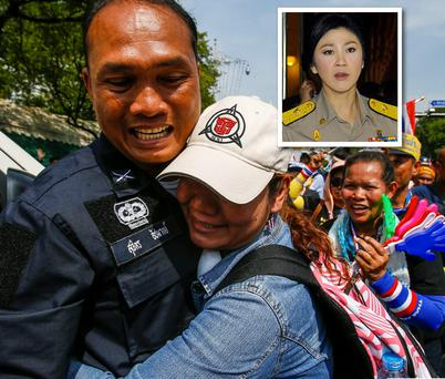 An anti-government protester hugs a riot policeman during a rally near in Bangkok. Inset: Thailand's Prime Minister Yingluck Shinawatra.