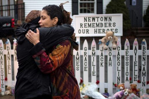 Women embrace after observing a moment of silence nearby Sandy Hook Elementary in Newtown