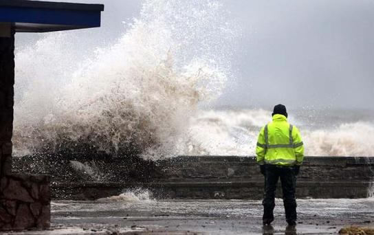 A man stands in front of a huge wave on the seafront in Rhyl as heavy seas and high tides sweep across the country Photo: PA